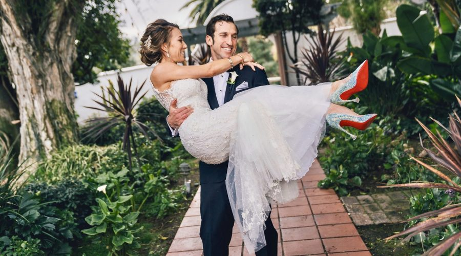 Groom holding bride wearing christian louboutin shoes at a church ceremony