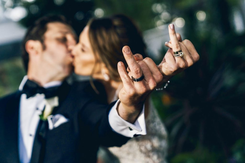 Bride and Groom showing off wedding bands while kissing