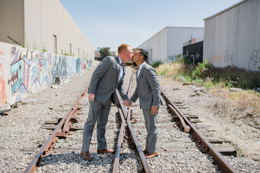Two grooms kissing on a railroad during first look photos