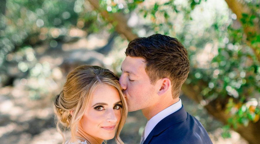 Groom kissing Bride's forehead in park