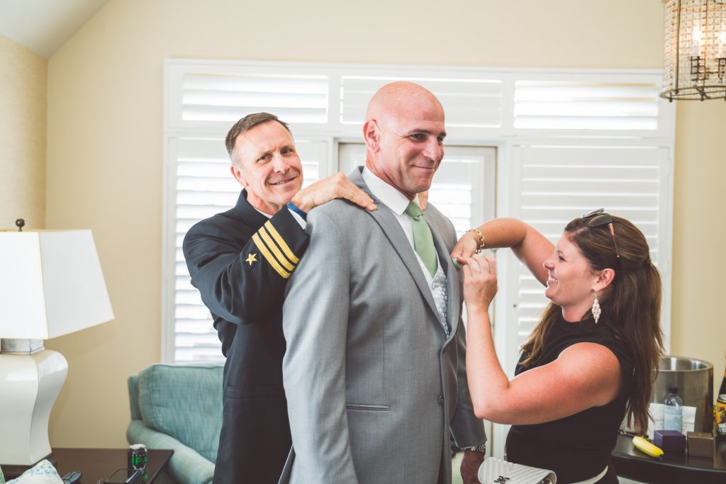 Wedding Planner pinning boutonniere on groom with Retired Navy Seal Officiant