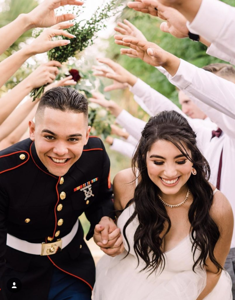 Military Bride and Groom holding Hands under human archway