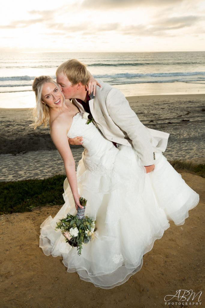 Bride and Groom kissing on Del Mar, CA beach with bridal bouquet at L'Auberge